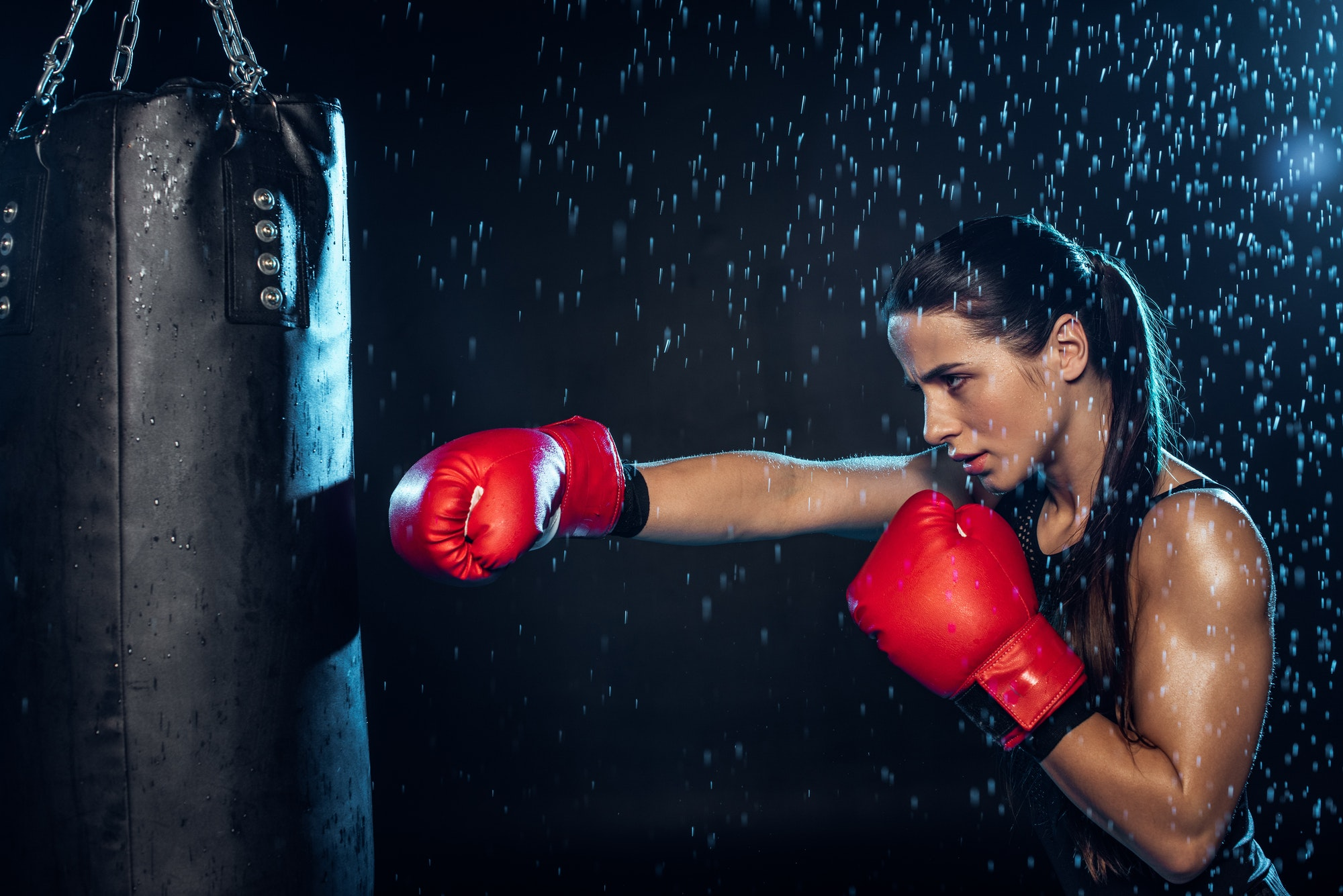 Pensive boxer in red boxing gloves training under water drops on black